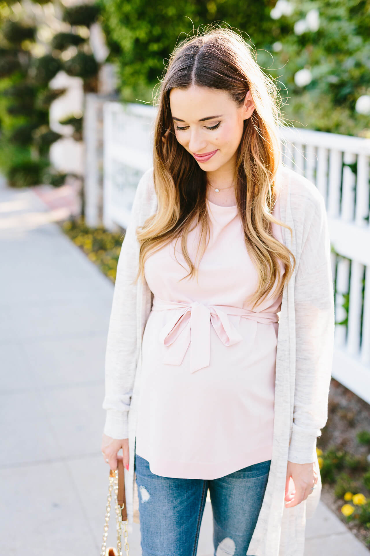 a pretty belted pink top with a light oatmeal-colored cardigan