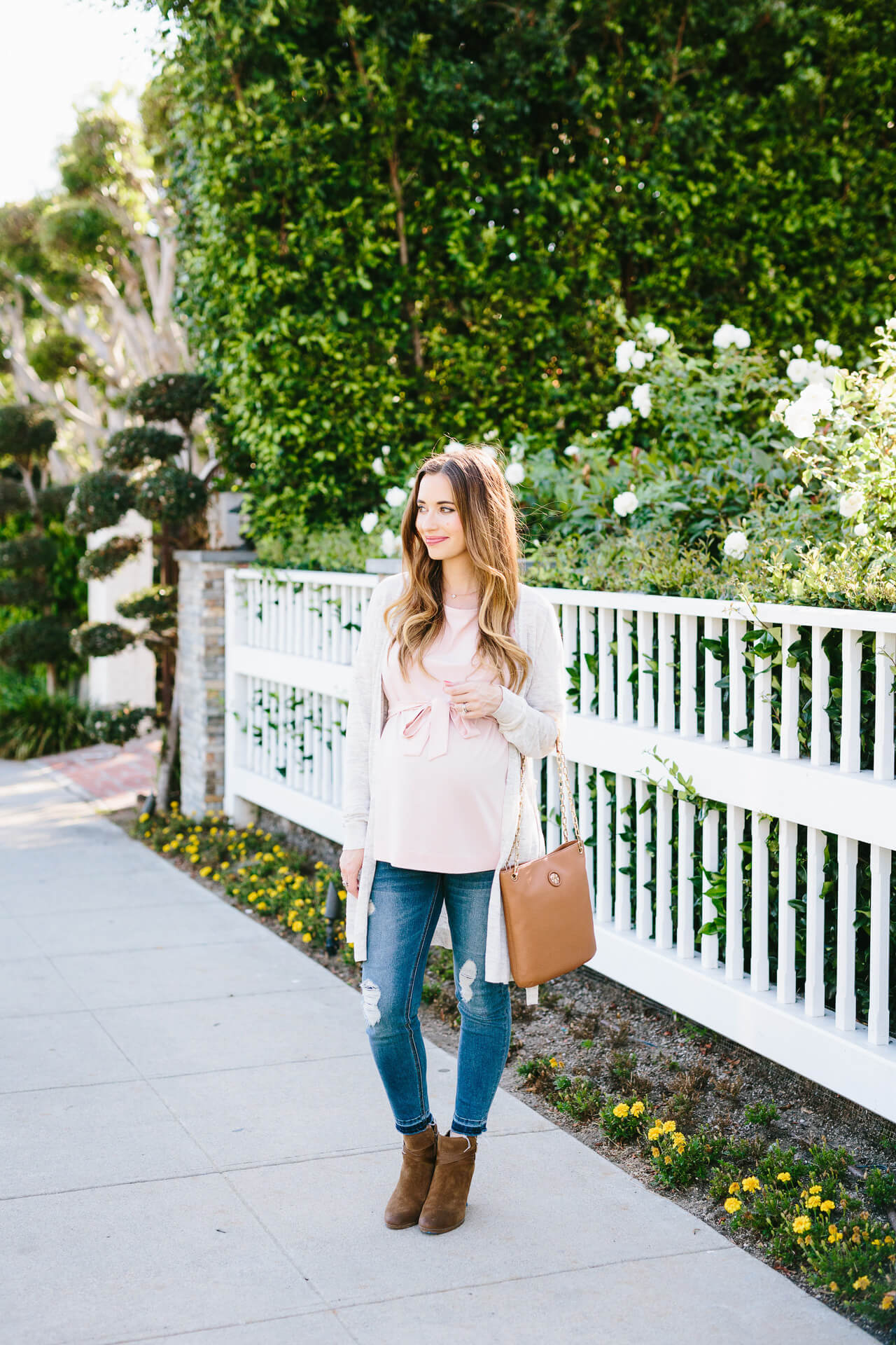 a casual summer outfit with a pink blouse and jeans