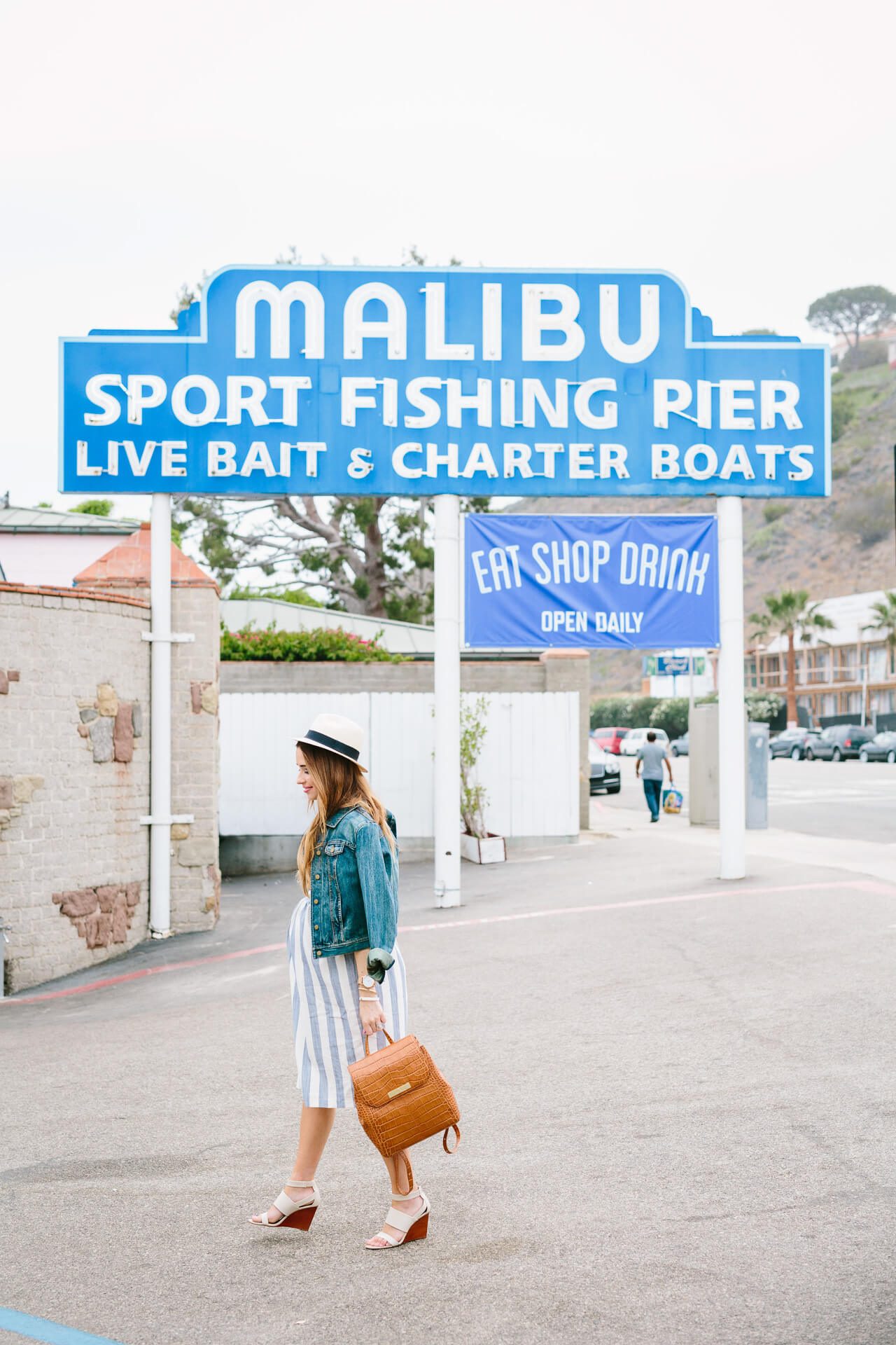 a day in Malibu wearing a striped shirtdress and a brown leather backpack