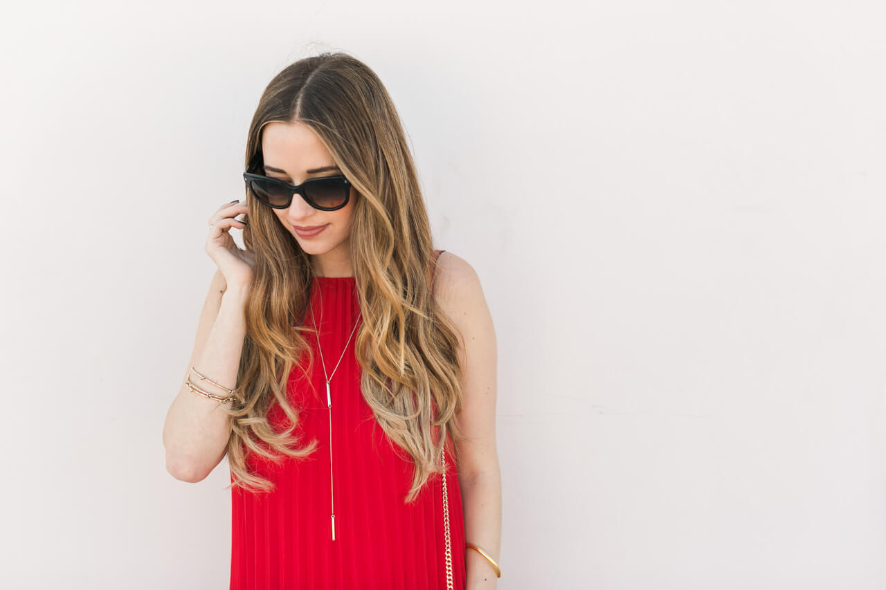red pleated dress outfit with black sunglasses