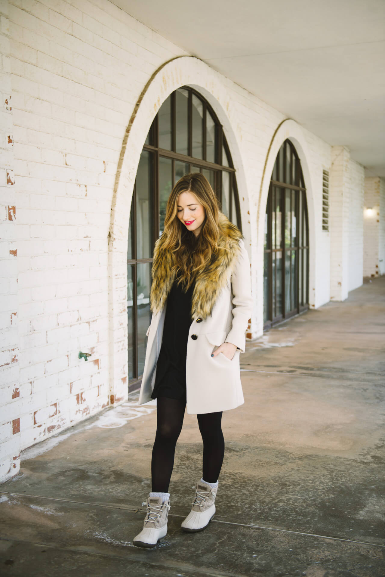 styling duck boots with a black turtleneck dress and a faux fur jacket