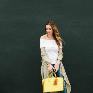 off the shoulder sweater with jeans and a beige duster