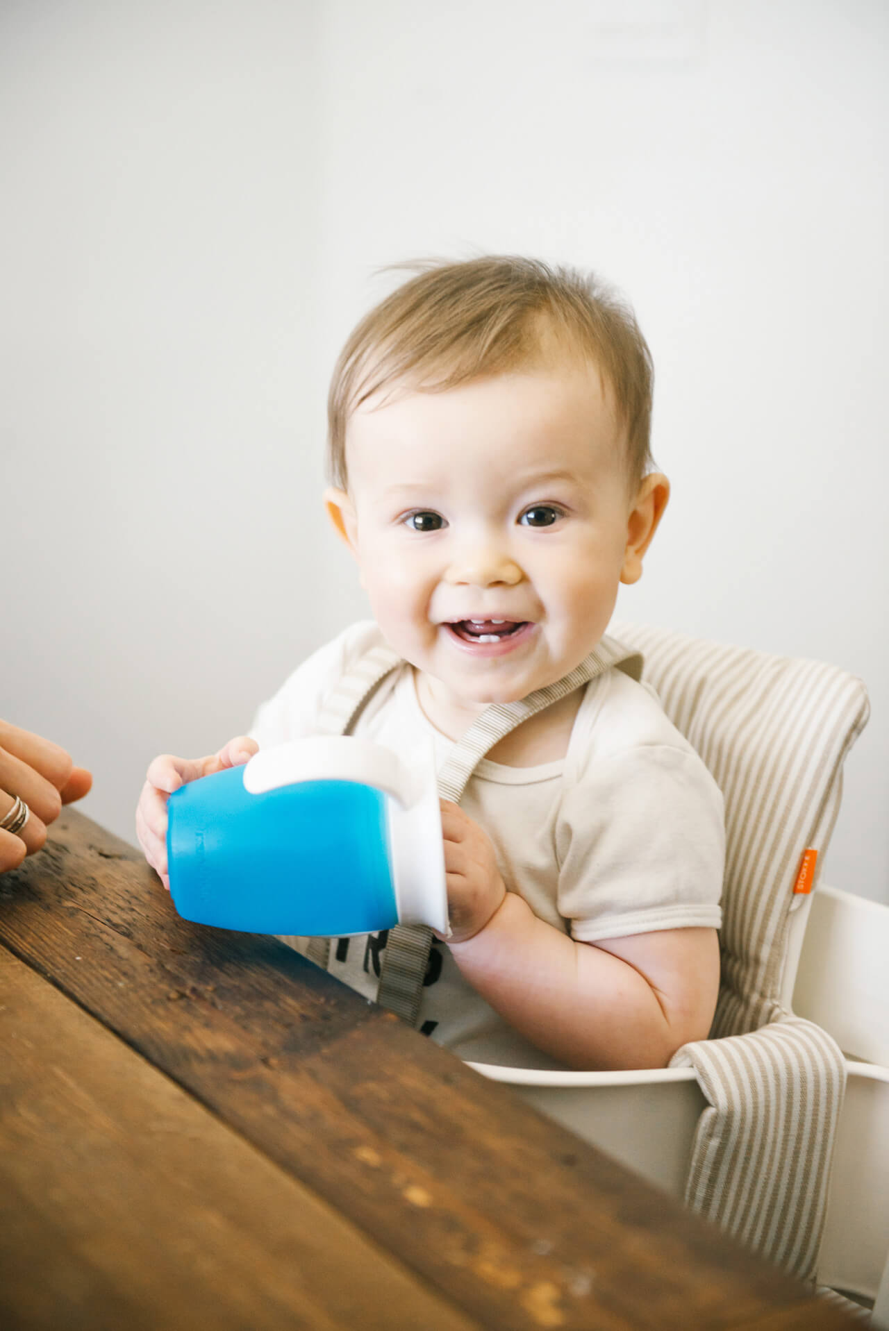 Smiling baby with his sippy cup ready for lunch