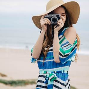 a day in manhattan beach with macy's wearing a colorful blue and green striped dress with cold-shoulder detail