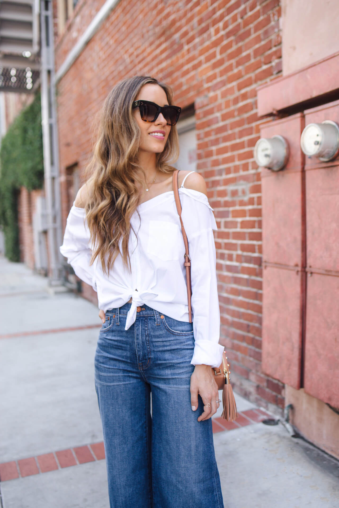 messy brunette waves with white off the shoulder top and wide leg jeans