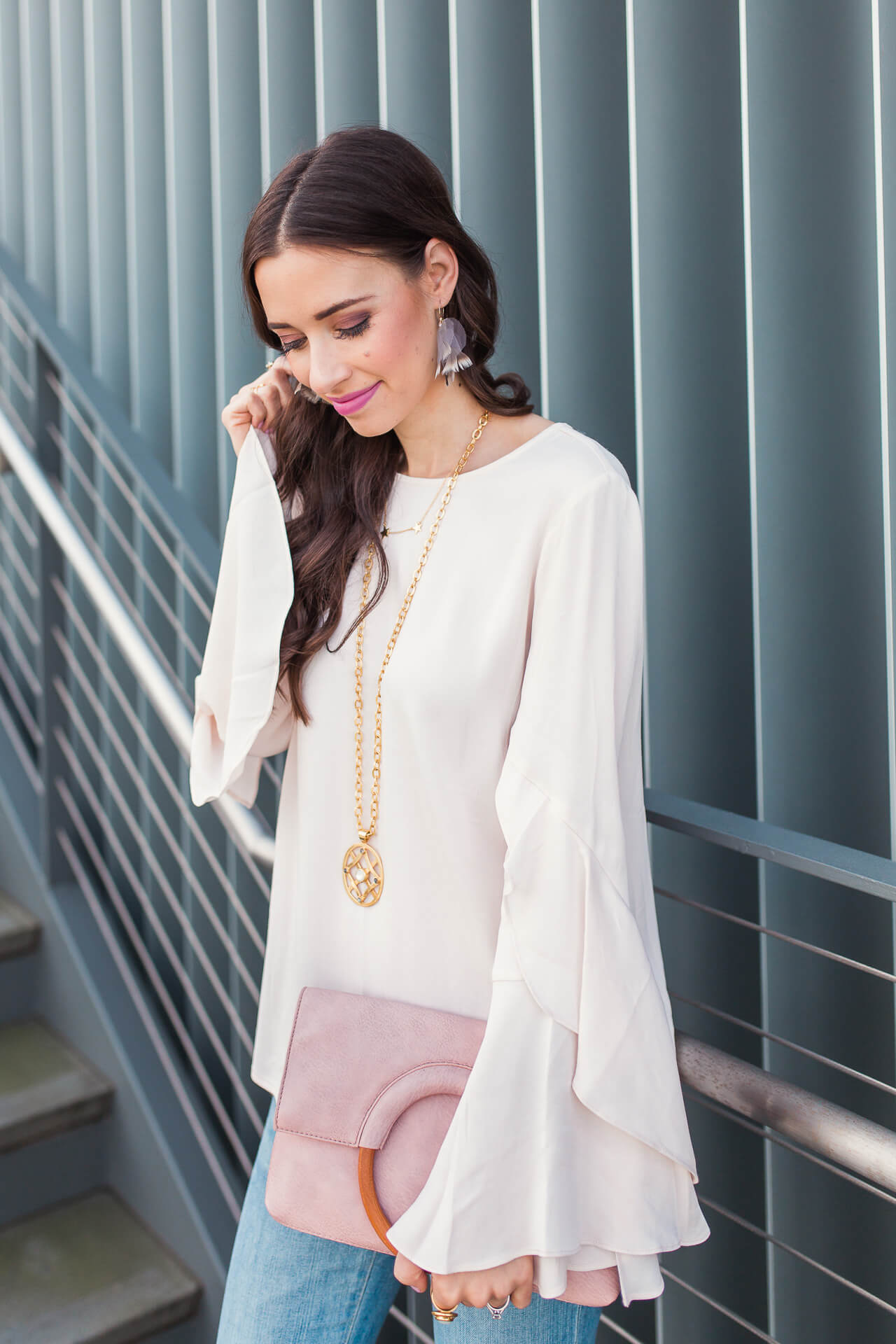 a feminine flowy blouse with a round handle bag