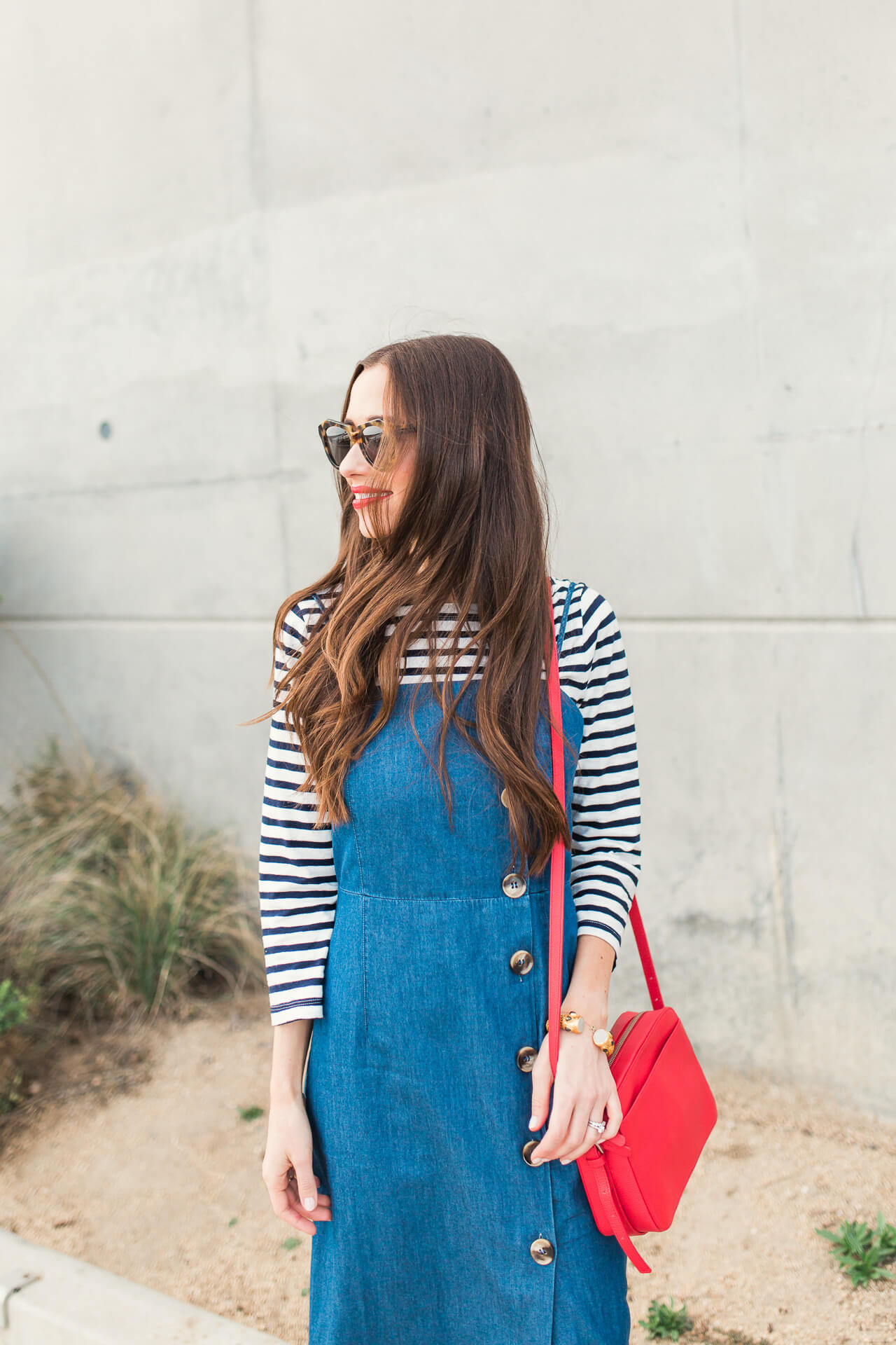 layering a denim dress with a striped shirt
