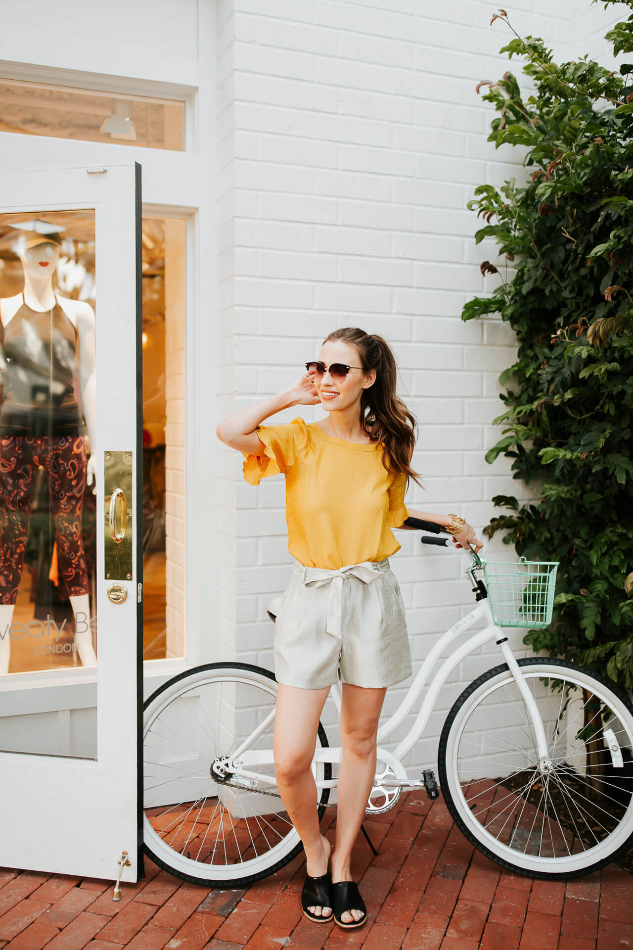 mustard blouse with linen shorts and black slides posing with bike - M Loves M @marmar