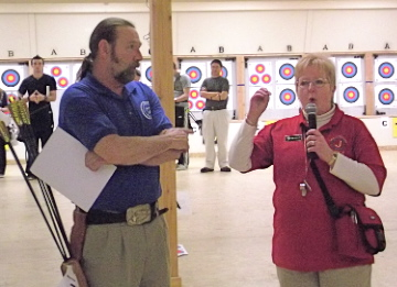 Reynold Sarns, left, is recognized by a competition judge for breaking a U.S. record in his barebow division.