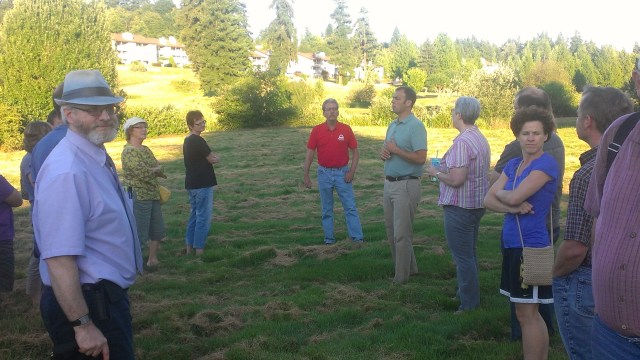 Ken Courtmanch (center,red shirt) and Curt Brees (teal shirt, tan pants) lead a short tour of the park site Tuesday night.