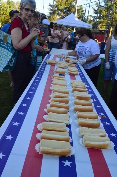Hot dogs were consumed by the hundreds, and were prepared production-line style.  Here a double-row of buns awaits the next batch of sizzling dogs from the grill. Thanks to Red Onion Burgers for supplying the buns! (Larry Vogel photo)