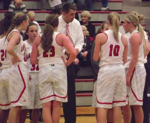 Hawks girls basketball coach Zach Wilde instructs his team during a second-half timeout.