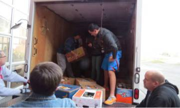 Students load the truck at the school for transport to the Concern for Neighbors Food Bank.