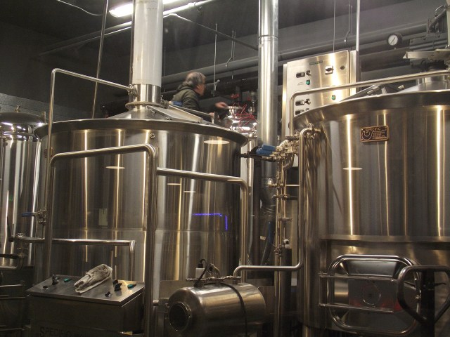 A technician works on the brewery equipment.