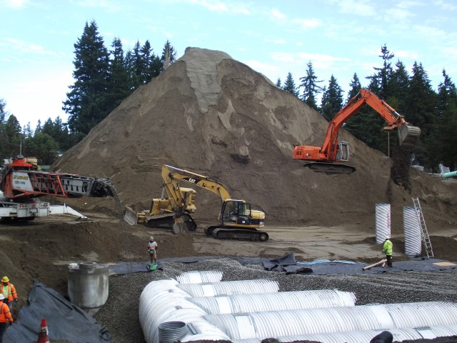 Work continues at the Town Center regional stormwater treatment facility. Crews have begun filling in the work site this week with gravel and dirt. Dirt not needed at the site will be used to improve a city service road near the Mountlake Terrace Recreation Pavilion. The underground stormwater facility and accompanying revamped parking lot for the Mountlake Terrace Library is expected to be completed this summer. (Photo by Doug Petrowski)