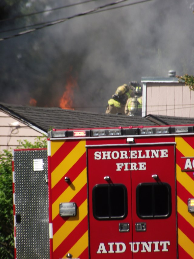 Flames shoot out of the house's attic crawlspace.