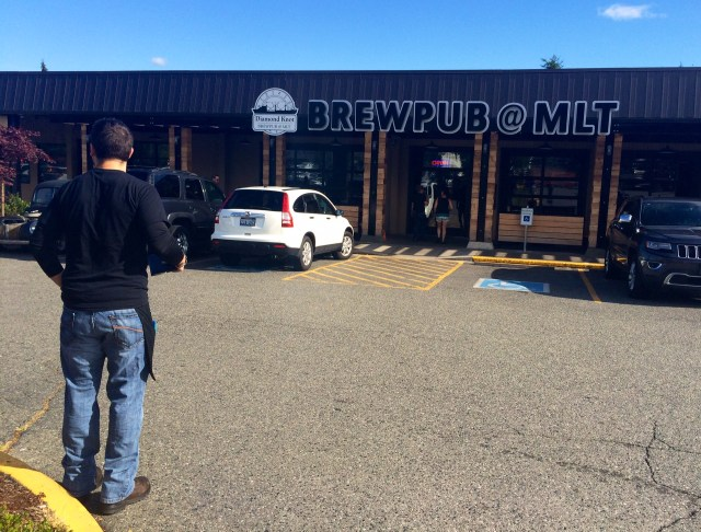 An employee of Diamond Knot Brewpub @ MLT steps out of the Mountlake Terrace establishment to view the brewpub's new sign, which was installed earlier in the day. (Photo by David Carlos)