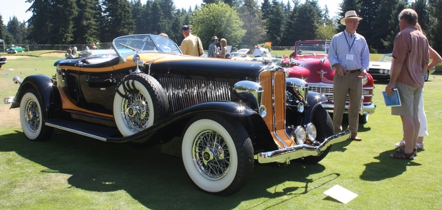 Owner Bruce Wanta chats with a spectator about his 1932 Auburn Boattail Speedster.