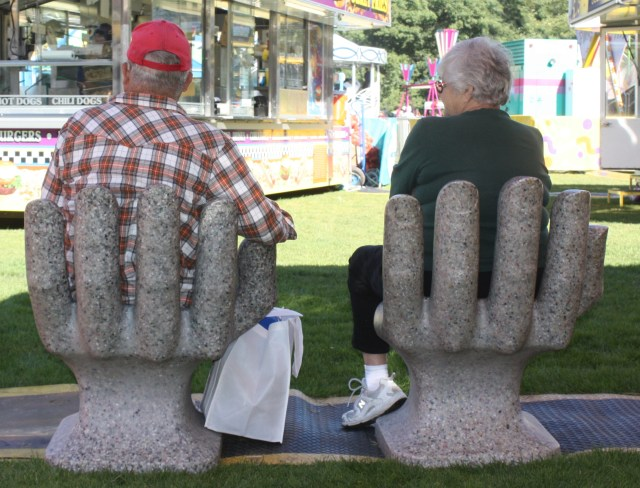 A couple took a breather on some unusual chairs.