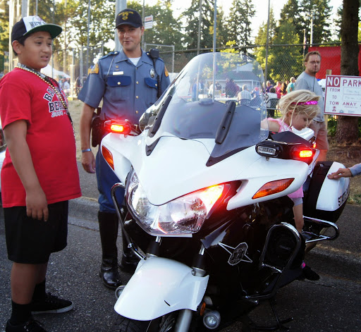 """A boy asks a police officer about law enforcement vehicles:  """"Is that all the colors you have, black and white?"""""""