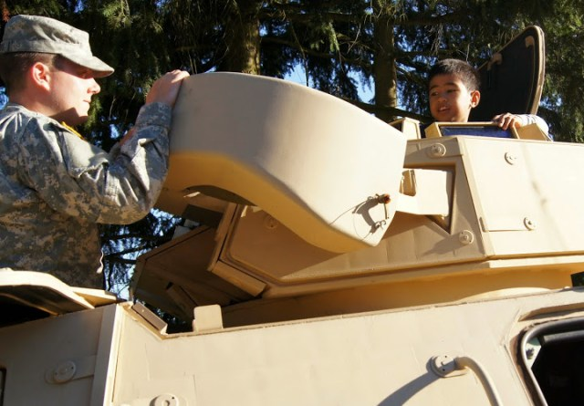A young fan peaks out of a turret of a National Guard ASV (Armored Security Vehicle).