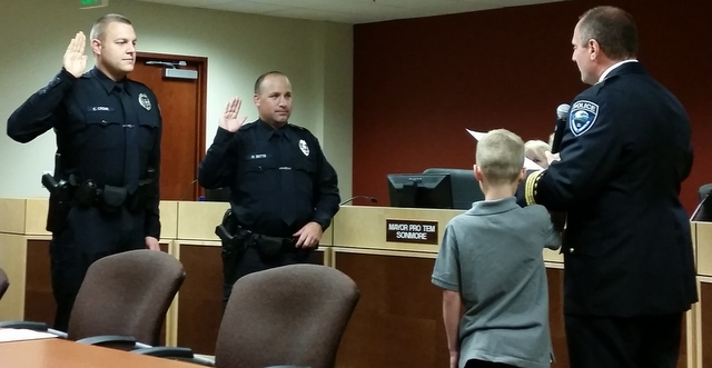 Here's a photo of Chief Greg Wilson Swearing in new Officers Carl Cronk (left) and Nathan Betts (right). A young family member holds the microphone for Chief Wilson.