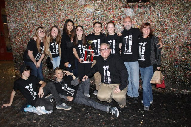 The Mountlake Terrace High School TheaterSports team poses in front of the famous gum wall outside the Market Theater in Seattle after picking up the fourth place trophy at Monday night's Hogan Cup finals, a competition of improv comedy for local high school drama departments. Also competing in the finals were Inglemoor, Bothell and Kamiak High Schools; Inglemoor took home first place honors. The MTHS troupe consists of Kyle Barton, Sage Cameron, Emily Davidson, Kimberly Fenn, Mikayla French, Tyler Grabarczyk, Kyle Henderson, Danielle Hirano and Cassie Stires, and is led by advisor Jeff Hogan (second from right) and drama department director Jeannie Brzovic (far right). (Photo by Amanda Petrowski)