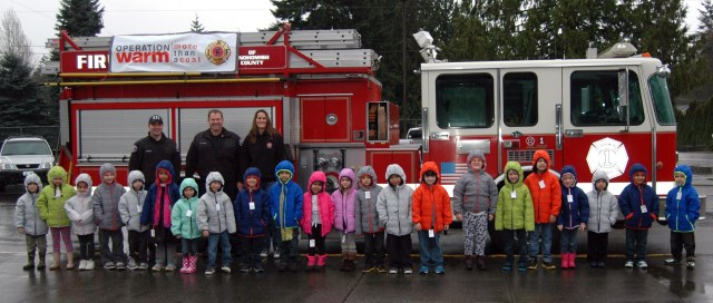 Kindergartners from Discovery Elementary show off the coats they received from Snohomish County Fire District 1 firefighters Micah Gaston, Capt. Rob Gullickson and Melissa Beard as part of the IAFF Firefighters Coats for Kids campaign. IAFF Local 1828 in Fire District 1 has provided coats for more than 150 children this year.