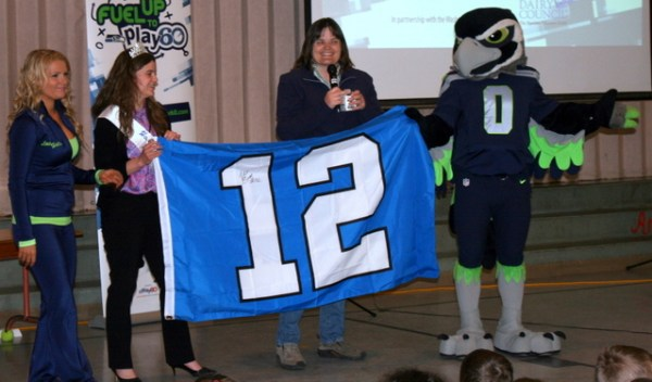 Washington Dairy Ambassador Janis DeJager and Dairy Farmer Leann Krainick  presented a 12th man flag authographed by Seattle Seahawk Michael Bennett to Mountlake Terrace Elementary School.