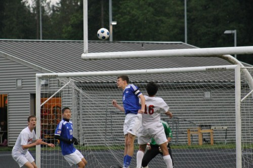 Shorewood's Callahan Gobel (#5, center) heads the ball away from Hawk Diego Aguiniga (#16) in front of the T-Bird goal.