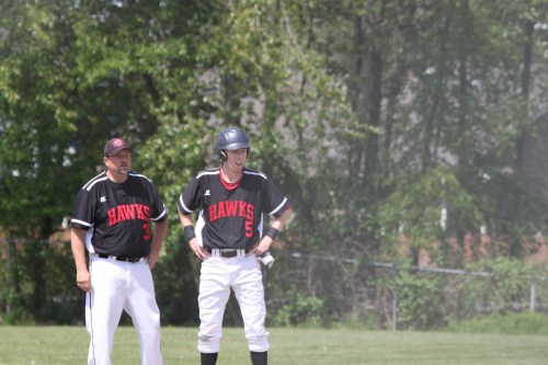 With Mountlake Terrace Coach Andrew Watters (left) watching, Drew Serres stands on third base after his bases-clearing triple in the second inning, giving the Hawks a 5-0 lead early in their District 1 first round game against Marysville-Pilchuck.
