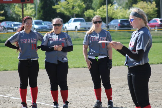 MTHS seniors (left to right) Cassandra Cariker, Hannah Wilcox and Sammy Harter were honored just before the first pitch of Wednesday's Mountlake Terrace - Lynnwood softball game at Mountlake Terrace High School. Freshman Jazz Zenk (far right) read notes about the three seniors during the short ceremony. (Photo by Doug Petrowski)