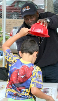 Snohomish County Fire District 1 firefighter Kuba Saidy helps Ethan McAvoy with a Firefighter's hat.