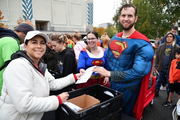 Edmonds Schools Foundation president Deb Anderson hands out race packets to a super pair of runners..