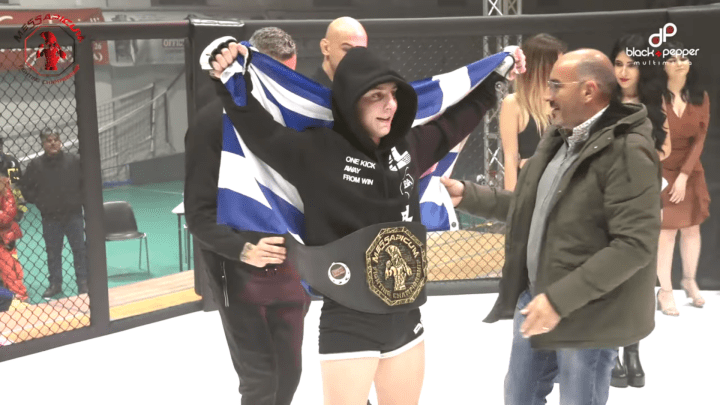 Alexandros Moumtzis gets the Messapicum Fighting Championship belt wrapped on him while he hoists the flag of Greece.