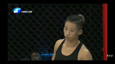 Liang Na stands in the cage while waiting for a fight to start.
