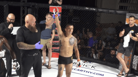 Jeff Molina gets his arm raised after winning an MMA fight.