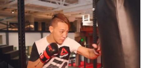 Rongzhu hits a punching bag while wearing MMA gloves.