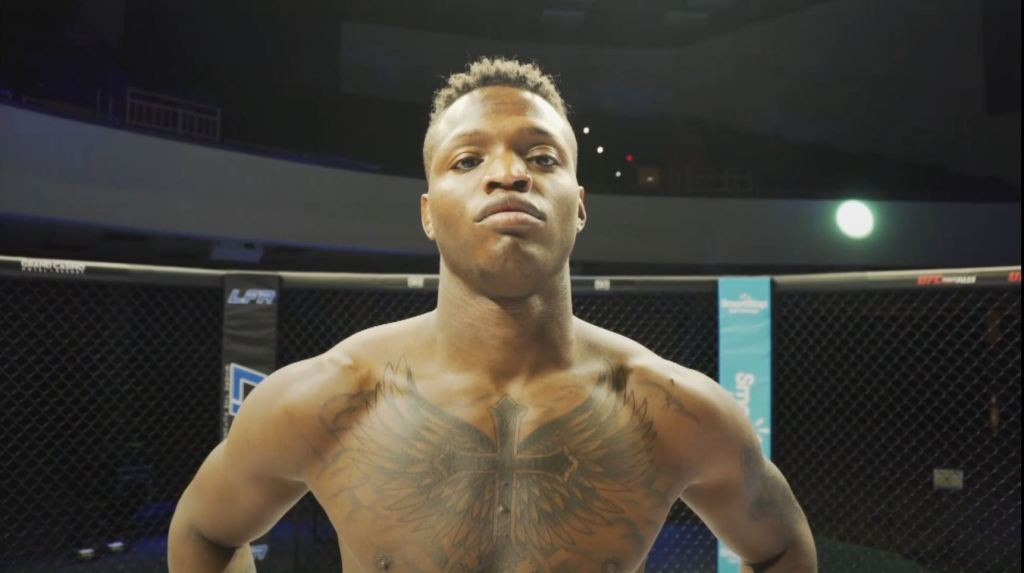 Terrance McKinney looks at a camera while standing inside the LFA cage.