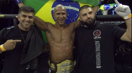 Gregory Rodrigues poses with two cornerman in the LFA cage while wearing an LFA belt and hoisting the Brazilian flag.