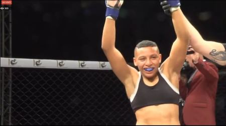 Josiane Nunes gets her arm raised in an MMA cage.