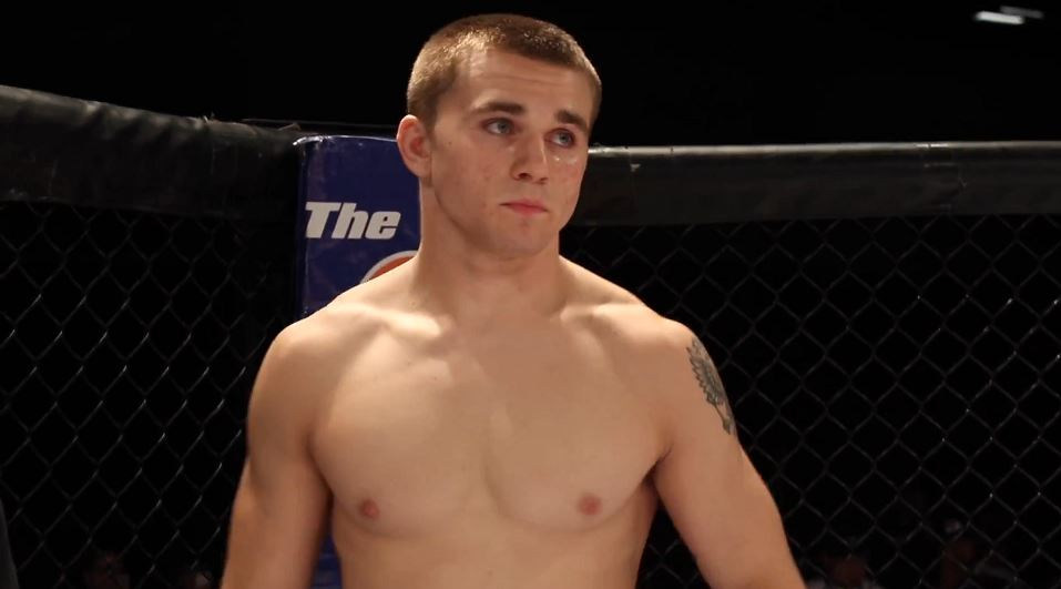 Nick Maximov stands in an MMA cage.
