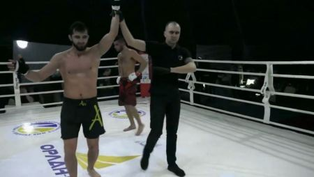 Liudvik Sholinian gets his arm raised inside an MMA ring.