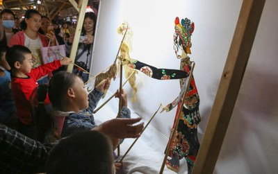 Children are experiencing shadow puppetry at the intangible cultural heritage fair in North Street, Xiangyang, Hubei Province.