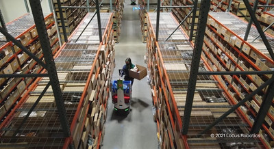 A LocusBot assisting one of evo's warehouse workers.