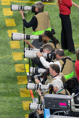 Canon's iconic white EF lenses and DSLR cameras alongside the sideline at The Big Game in Minnesota.