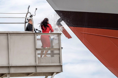 Ship sponsor Jodi J. Greene breaks a bottle of sparkling wine across the bow during the christening ceremony for the nation's 21st Littoral Combat Ship, the future USS Minneapolis-Saint Paul.