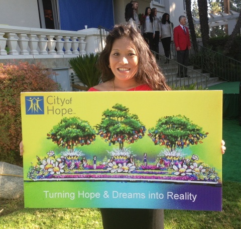 Cancer survivor, Christine Pechera, holding a rendering of City of Hope's 2014 Rose Parade float at...
