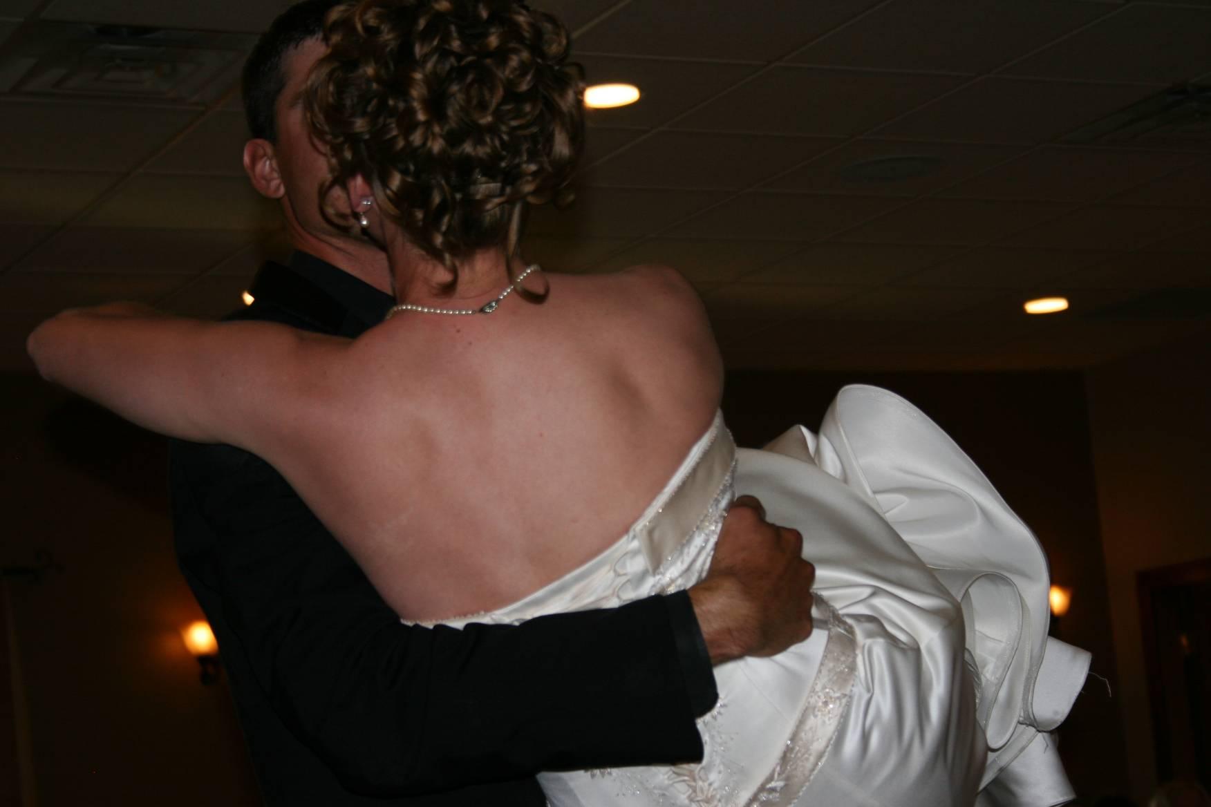 Corey carries his bride into the wedding reception.