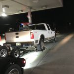 Super America gas station towing a heavy duty truck with wrecker